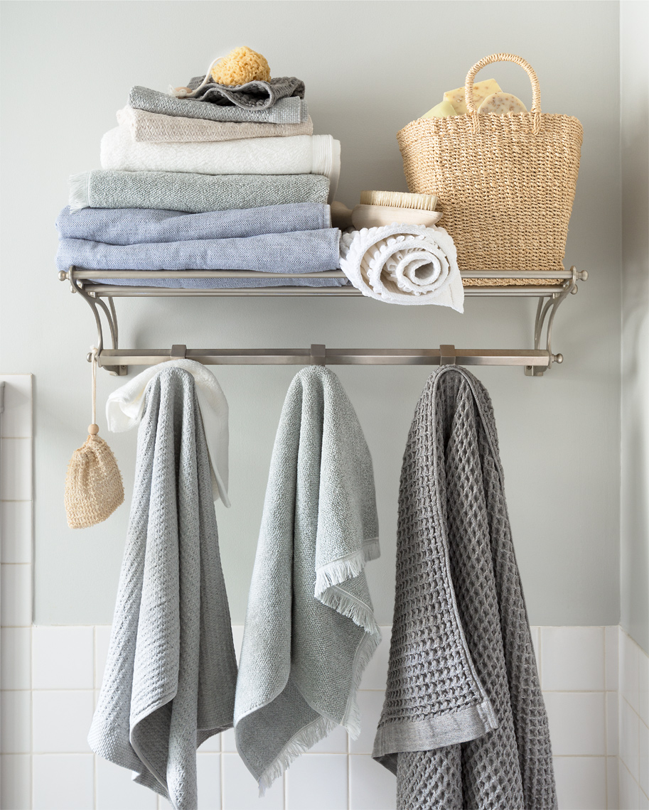 Bathroom towel rack with white, grey, pale blue towels and a whicker basket.